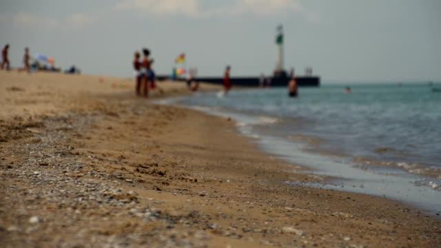 stockvideo's en b-roll-footage met sunny beach scene on lake with happy people - vlag