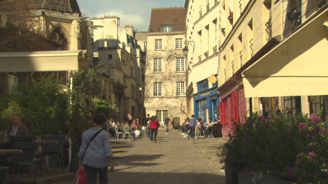 Sunny cobbled lane way with colorful shop fronts and restaurants lining the streets Traditional style French buildings line the lane way with a...