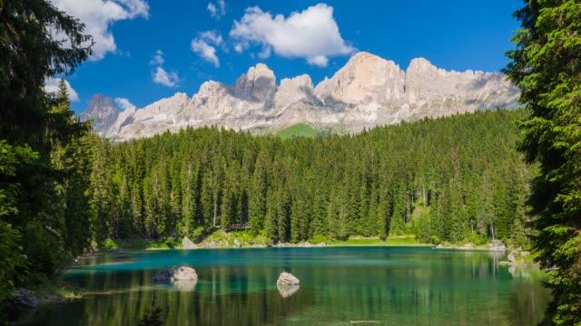 sunny day at italian lake carezza in trentino-alto adige in dolomites, italy - dolomites stock videos & royalty-free footage