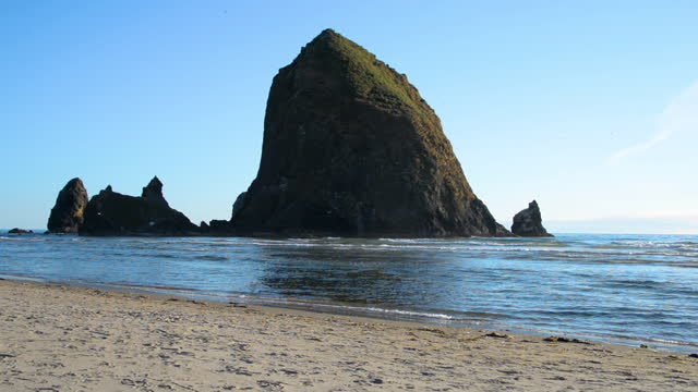 sunny day on a beach near the haystack rock in cannon beach - haystack rock stock videos & royalty-free footage