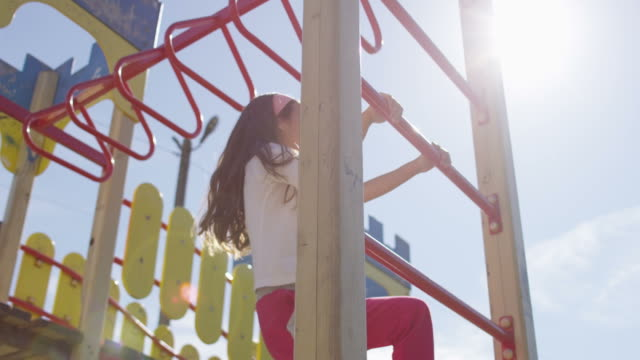 sunny day on playground girl on overhead climber - jungle gym stock videos and b-roll footage