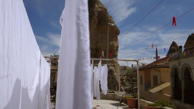 vídeos y material grabado en eventos de stock de sunny day view of cave homes - cappadocia, turkey - cuerda de tender la ropa