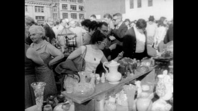 vídeos de stock, filmes e b-roll de / sunny morning at the flea market / sign that reads: 'this is a flea market come fleece me!' / tourists browse the antiques / tables of knick... - mercado das pulgas