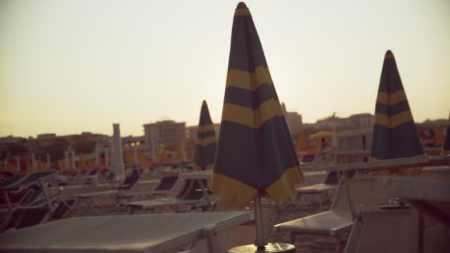 vídeos de stock, filmes e b-roll de sunny rimini beach – mid shot of beach loungers and sunshades - chapéu de sol