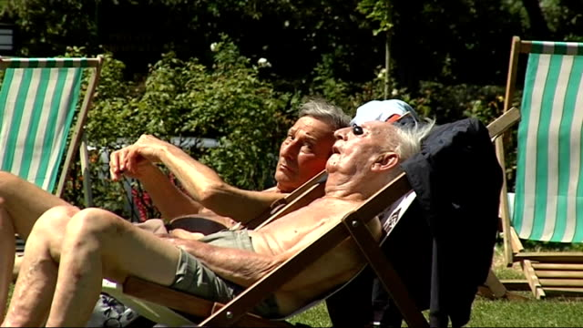 sunbathers on south bank hyde park / gvs london zoo woman sitting reading newspaper older people sunbathing in deckchairs rose gardens and people... - deckchair stock videos & royalty-free footage