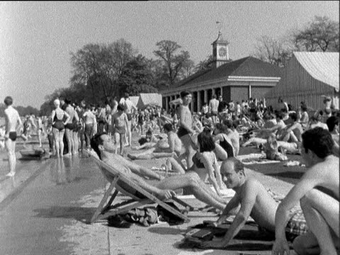 vídeos de stock e filmes b-roll de southend crowds on the beach ferris wheel in motion girl in bikini walks with another in scoopback swimsuit serpentine lido crowd sitting at lido boy... - liverpool inglaterra