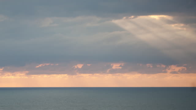 Sunrays shine through clouds over ocean