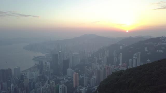 vídeos de stock, filmes e b-roll de vista aérea do nascer do sol, voando a aeronave de uma cidade de hong kong com desenvolvimento edifícios, transportes, infra-estrutura de alimentação de energia - distante