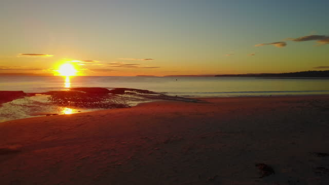 stockvideo's en b-roll-footage met 4k sunrise aerial view of an empty huskisson beach, australia - horizon over water