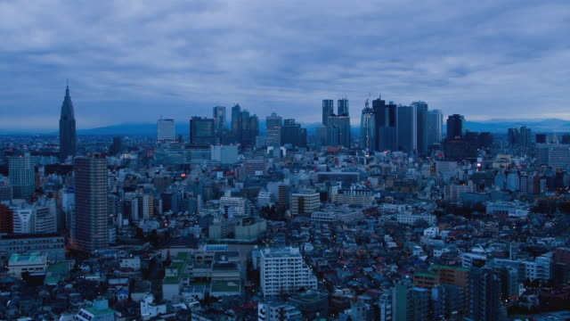 WS T/L Sunrise and clouds passing over Shinjuku business, shopping and entertainment district / Tokyo, Japan