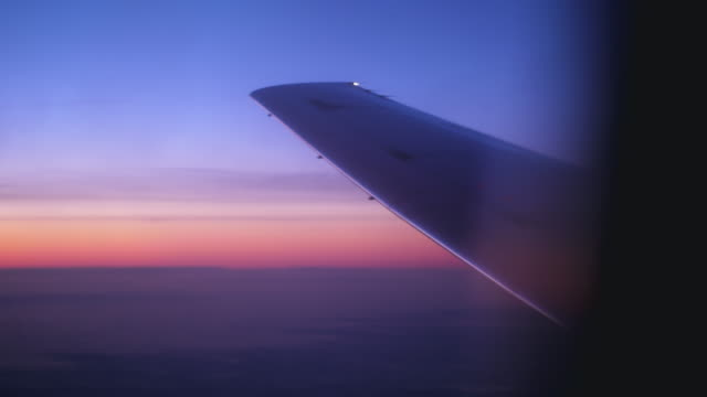 stockvideo's en b-roll-footage met zonsopgang en wing uitzicht vanuit lucht vliegtuig raam - silhouet