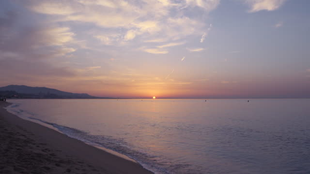 4k: sunrise at badalona (barcelona) beach at the end of the summer. we can see the calm mediterranean sea in a symmetric wide angle shot with the sun and the horizon in the middle. - 静かな情景点の映像素材/bロール