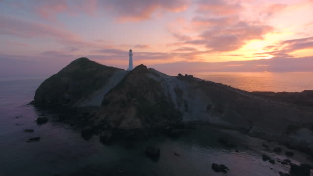 sunrise at castlepoint lighthouse. - new zealand stock videos & royalty-free footage