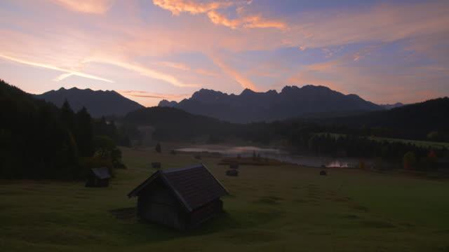 sunrise at lake geroldsee (wagenbrüchsee) with karwendel mountains in background. geroldsee, krün, garmisch-partenkirche, werdenfelser land, karwendel, bavaria, germany. - karwendel mountains stock videos and b-roll footage
