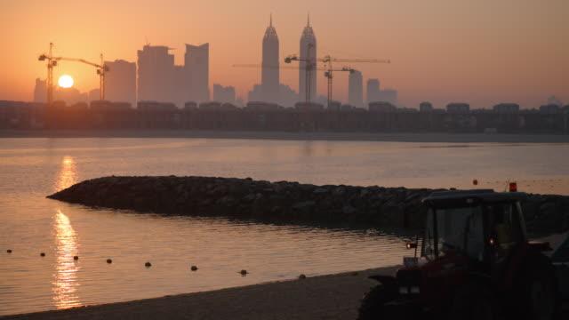 sunrise at luxury apartment hotel complex - palm island, dubai - crane stock videos & royalty-free footage