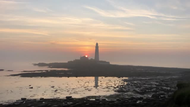 stockvideo's en b-roll-footage met sunrise at st mary's lighthouse in whitley bay the uk could encounter the hottest july day on record later this afternoon - whitley bay