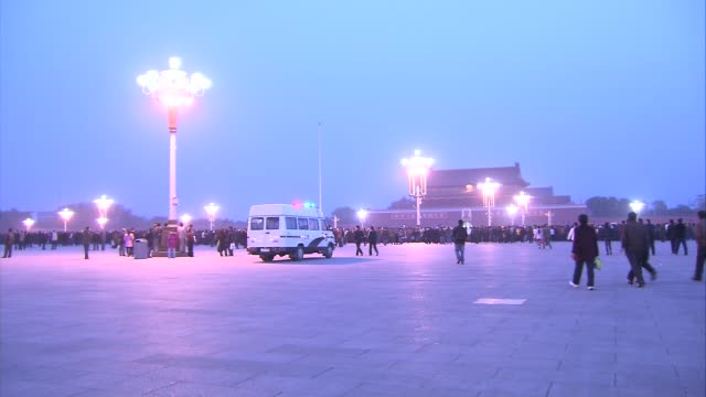beijing tiananmen square people walking in square in early morning with lights still on gate of heavenly peace in background bird of prey flying... - tiananmen gate of heavenly peace stock videos & royalty-free footage