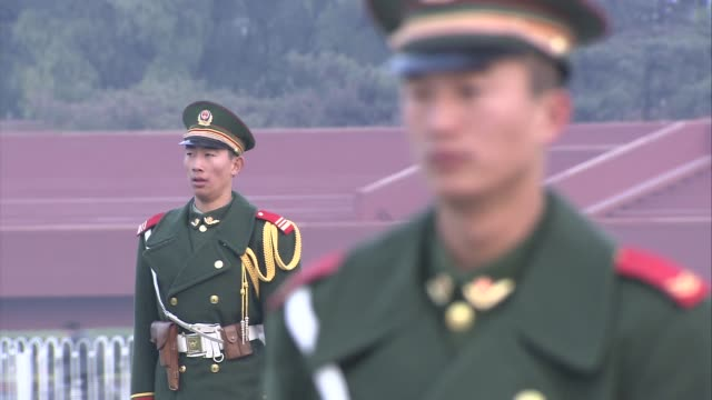 sunrise at tiananmen square soldier in uniform standing guard in front of the gate of heavenly peace with portrait of mao zedong visible in... - tiananmen gate of heavenly peace stock videos & royalty-free footage
