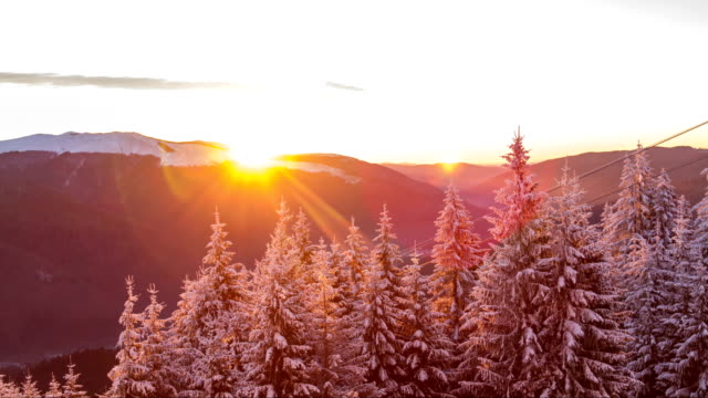 Sunrise at winter forest mountains