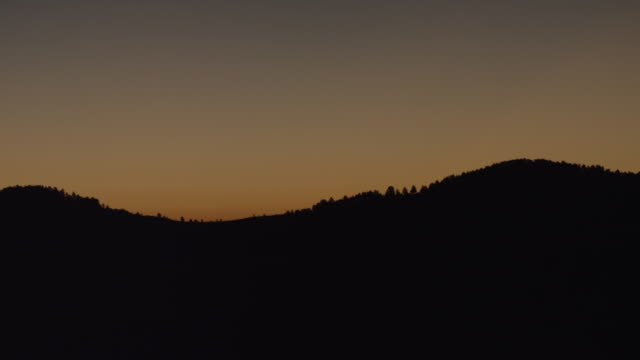 ws pan sunrise behind at silhouetted mountain / custer state park, south dakota, united states - カスター州立公園点の映像素材/bロール