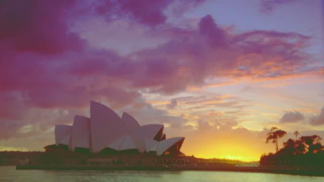 sunrise behind harbor + sydney opera house / sydney, australia - bennelong point stock videos and b-roll footage