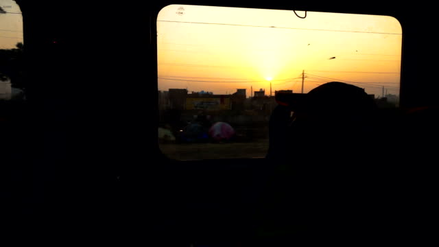 Sunrise by traveling train window in India