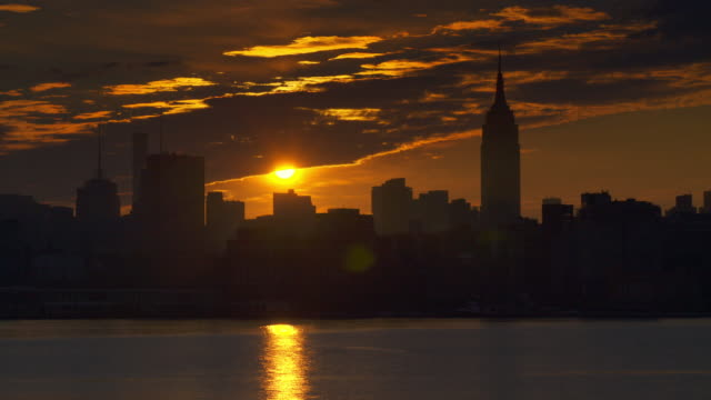 sunrise creeping out from underneath thick cloudscape above new york city skyline along hudson river. - 逆光点の映像素材/bロール