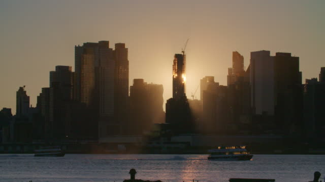 Sunrise cuts through skyscraper being constructed illuminating ferries moving along Hudson River.