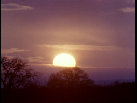 t/l sunrise, emerging from cloud then disappearing again. trees on horizon - emersione video stock e b–roll