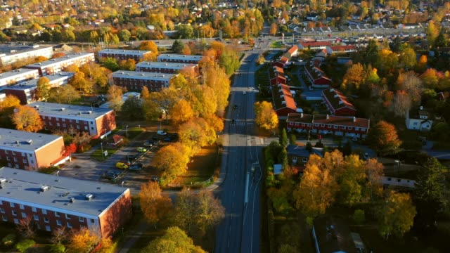 sunrise. flying over suburban stockholm, apartment buildings, villas, road - svezia video stock e b–roll