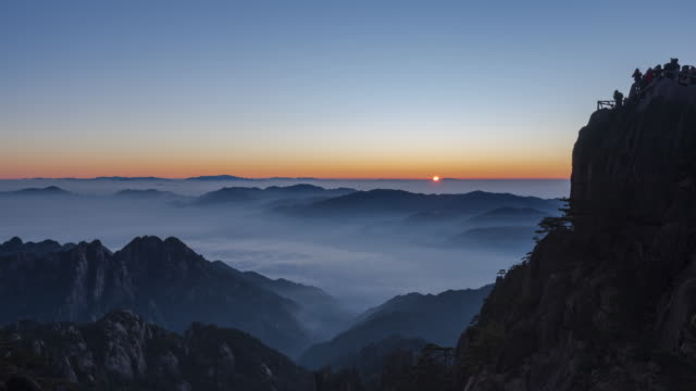 sunrise from bright top peak of huangshan mountain - tilt down - time lapse - sequential series stock videos & royalty-free footage