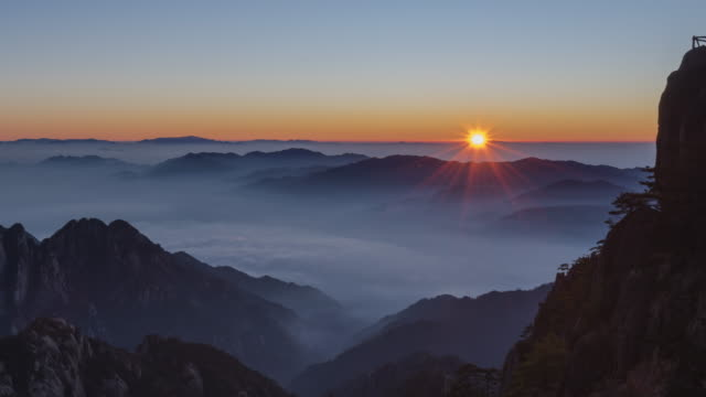 vídeos de stock e filmes b-roll de sunrise from bright top peak of  huangshan mountain - time lapse - nevoeiro
