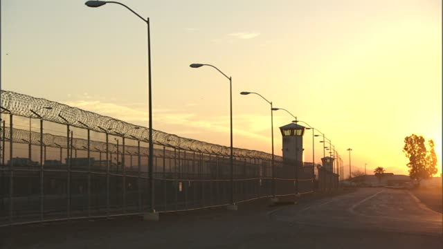 vidéos et rushes de a sunrise glows over a prison complex. - prison
