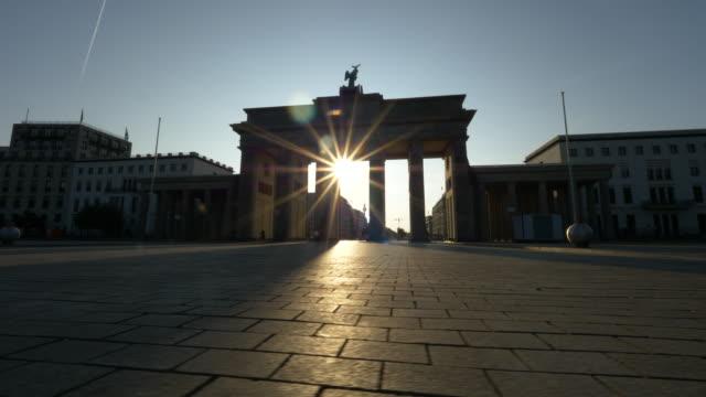 vídeos de stock e filmes b-roll de sunrise in brandenburg gate, berlin - portão