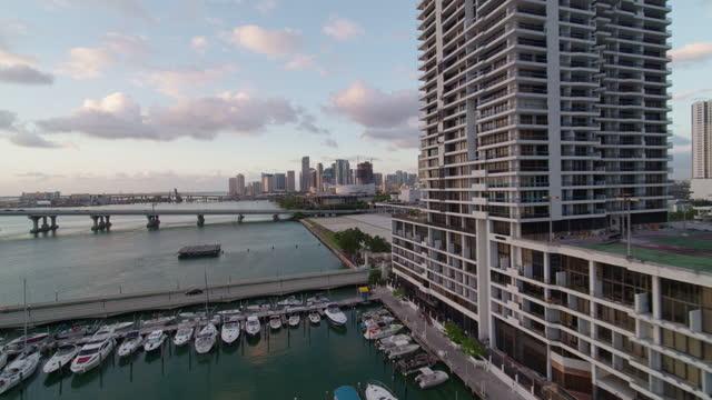stockvideo's en b-roll-footage met zonsopgang in downtown miami, het uitzicht over de jachthaven vanaf biscayne bay. luchtvideo met het doorsturen en panning filmische camerabeweging. - venetian causeway bridge
