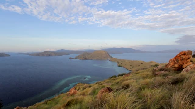 Sunrise in Komodo from a hill with grass and rocks