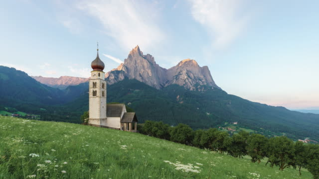 sunrise landscapes of church st. valentin on grassy hilltop with view of rugged peaks of mountain schlern with alpenglow in background in the valley of south tyrol, italy, europe - siusi video stock e b–roll