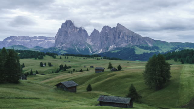 sunrise landscapes on alpe di siusi with sassolungo or langkofel mountain group in background and small cabins on grassland in summer, south tyrol, italy - langkofel stock videos & royalty-free footage