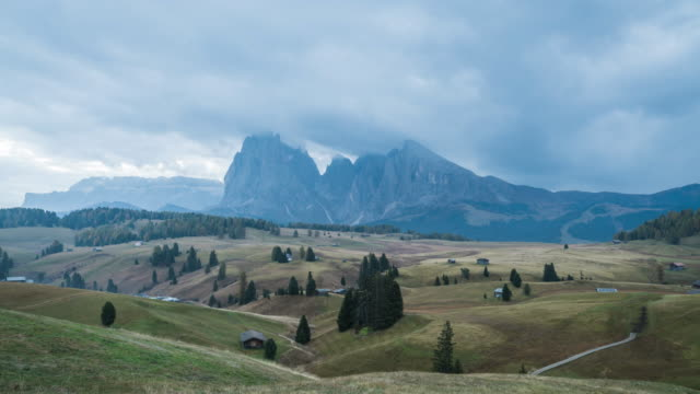 sunrise landscapes on alpe di siusi with sassolungo or langkofel mountain group in background and small cabins on grassland in summer, south tyrol, italy - alpe di siusi video stock e b–roll