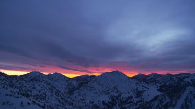 ws t/l sunrise light flooding clouds over snowy peaks / alta, snowbird, utah, usa  - alta stock-videos und b-roll-filmmaterial