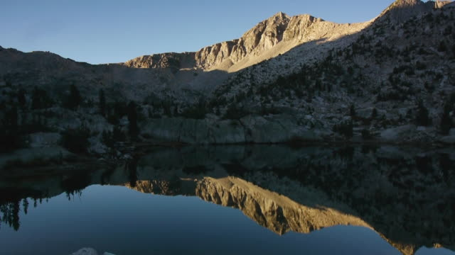tl sunrise light illuminates wilderness mountain range, reflecting in lake, kings canyon national park, sierra nevada mountains, california - nevada stock-videos und b-roll-filmmaterial