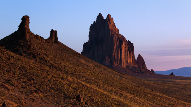 vídeos de stock, filmes e b-roll de t/l sunrise light on shiprock above the high-desert plain of the navajo nation in san juan county, new mexico, usa - novo méxico
