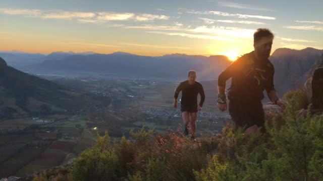 vidéos et rushes de les coureurs de montagne de lever de soleil courant vers le haut - qui monte