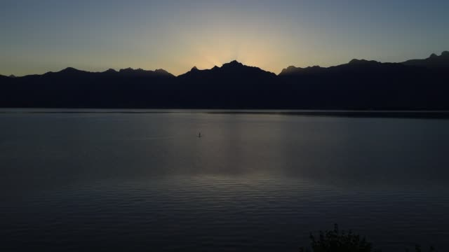 sunrise moves behind the alps on lake geneva on august 9, 2020 in saint gingolph, switzerland.the village has a specific geographical position being... - atmosphere filter stock videos & royalty-free footage
