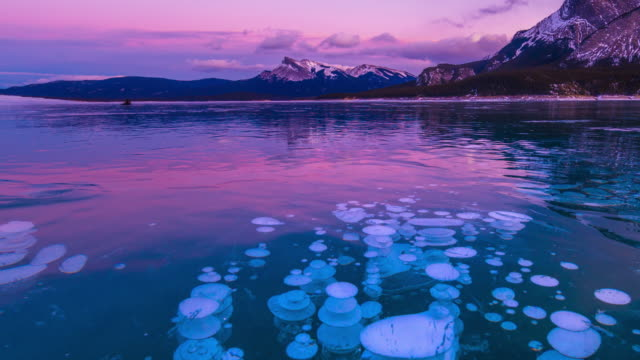 sunrise of frozen lake with ice bubble -time lapse - cave stock videos & royalty-free footage