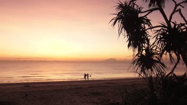 sunrise on beach, two people walking briskly - tanzania stock videos & royalty-free footage