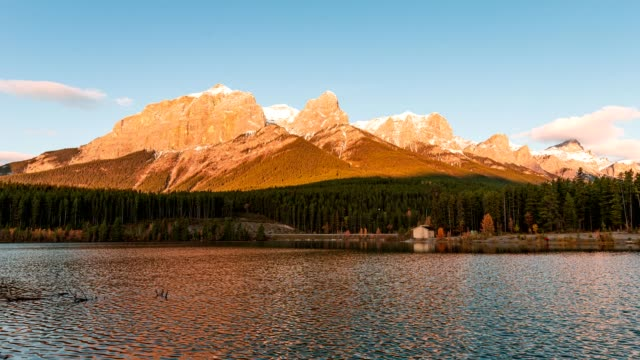 sunrise on mount rundle with blue sky on rundle forebay reservoir in autumn at canmore, canada - alberta stock videos & royalty-free footage
