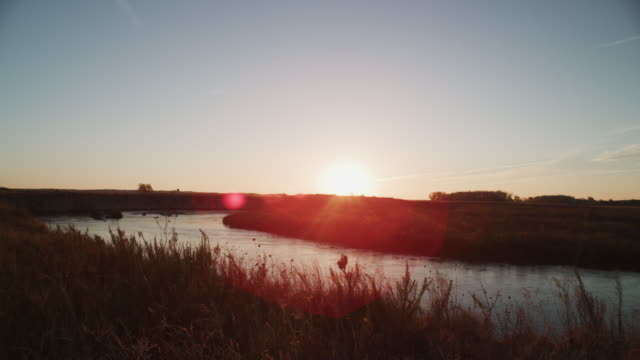 sunrise on the prairie landscape; sun refracts in lens as it rises in the east over the dismal river. - prairie stock videos & royalty-free footage