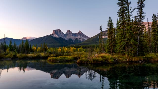 sunrise on three sisters mountains with pine forest reflection on pond at canmore - banff stock videos & royalty-free footage