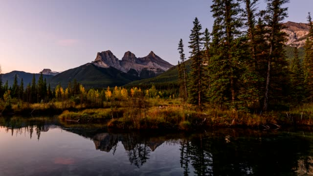 sunrise on three sisters mountains with pine forest reflection on pond at canmore - tre oggetti video stock e b–roll